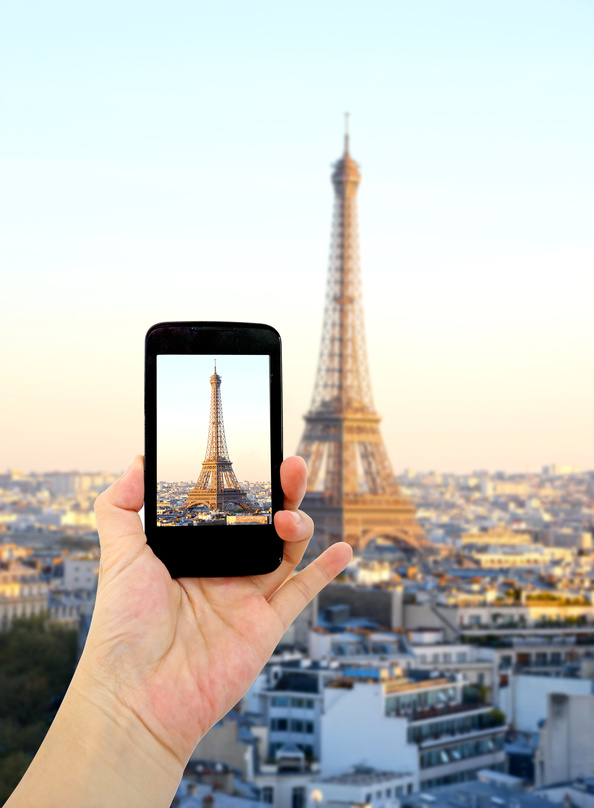 Woman hand taking pictures in front of Eiffel Tower, Cell phone